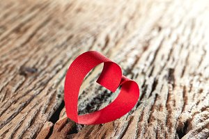 Red ribbon heart on wooden