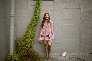 Girl Smiling by Brick Wall