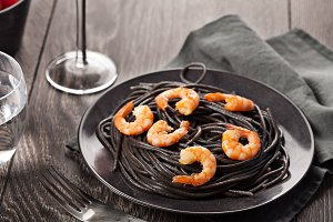 Black italian pasta with shrimps food on dark background