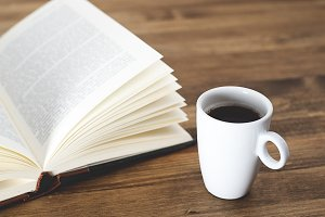 Cup of coffee with a book on rustic wooden table