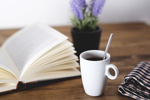 Cup of coffee with a book on rustic wooden table with a flower in the background