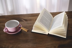 Cup of coffee with a book on wooden table