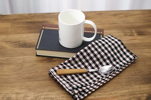 Cup of coffee and a spoon with a book on wooden table