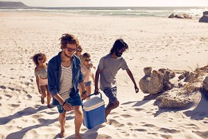 Group of friends carrying cooler