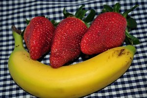 banana lying and strawberries on it