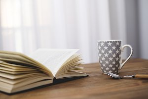 Cup of coffee with a book on wooden table.