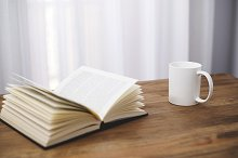 White cup of coffee with a book on wooden table.