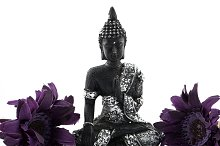 Figure of Buddha with two flowers on white background