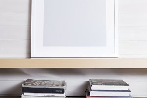 White picture frame sitting on a wooden shelf with books