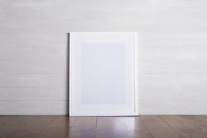 White picture frame leaning on wall