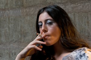 young woman smokes cigarette