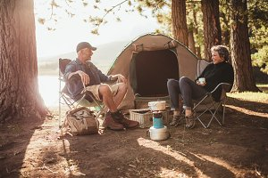 Couple relaxing on chairs by tent