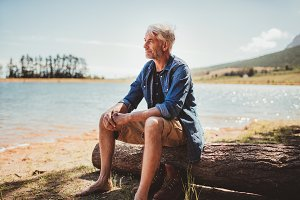 Mature man sitting on a log