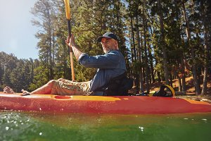 Senior man paddling a kayak
