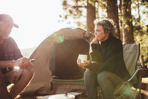 Relaxed couple sitting outside tent