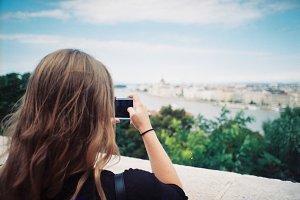 Girl photographing city panorama