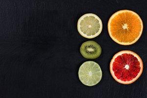 Sliced citrus fruit on slate