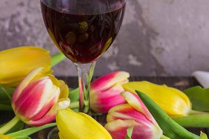 Glass of red wine and fresh tulips