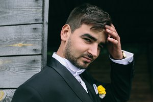 young handsome groom posing and looking at the camera