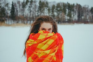 A girl wrapped in orange blanket