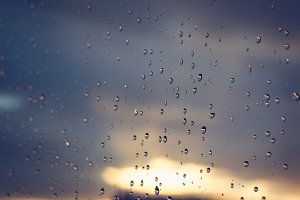 Raindrops on Window with Sunset