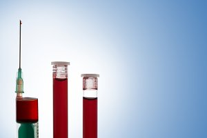 Syringe and 2 vials blood closeup