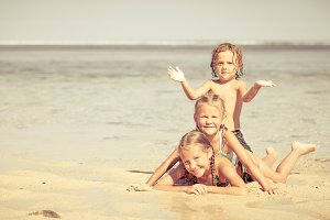 three happy kids playing on beach