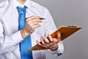 Businessman holding folder and pen
