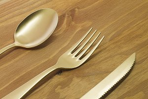 Spoon, fork and knife on wooden table