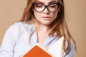 Girl with glasses holds a notebook.