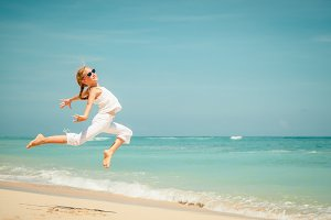 teen girl jumping on the beach