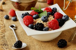 oatmeal with berries on a wooden table, selective focus