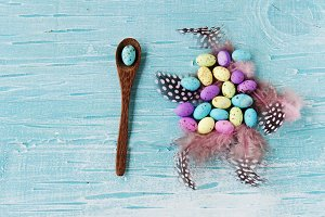 Easter colored eggs, feathers, blue wooden