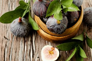 raw figs in a wooden bowl, selective focus