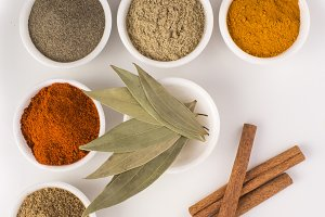 Spices and Herbs in bowls on white