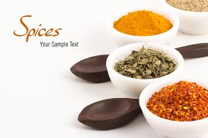 spices and herbs with wooden spoons