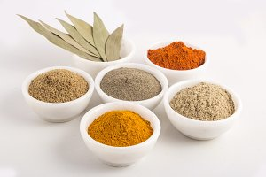 spices and herbs in white bowls