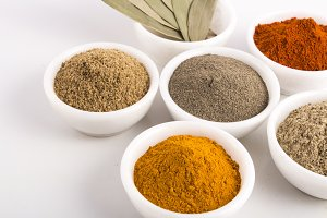 various spices in white bowls