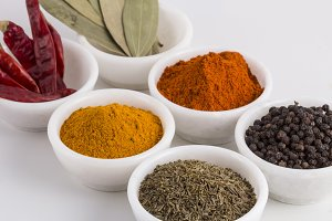 various indian spices in white bowls