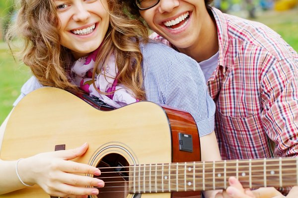 Teens with guitar in park