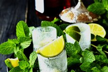ice glasses of whiskey with mint and lemon