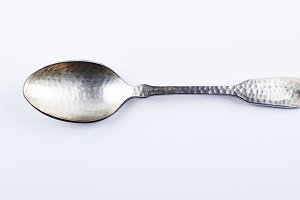 Old metal spoon on white background