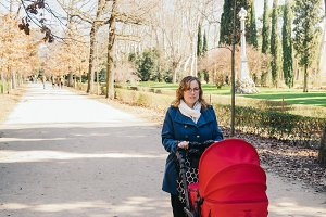 Mother walking with baby stroller