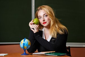 Geography teacher holding apple.