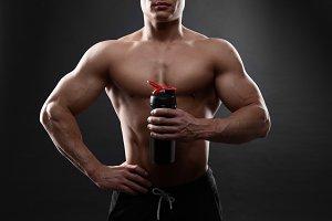 Man bodybuilder is holding a shaker for drinks