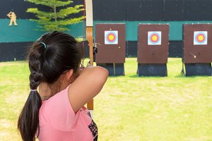 Girl holding and aiming bow