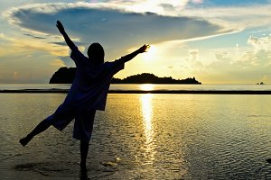 Woman happy at beach in sunrise