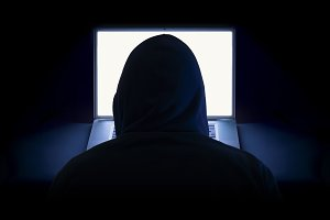 Hacker with hoodie and laptop