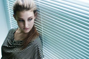 Girl at the window with blinds