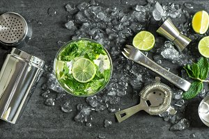 Glass of cocktail with lime, mint